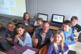 Ehrenamt im Ruhestand: Älterer Mann inmitten von Schülerinnen und Schülern bei der PC-Nachhilfe. Der SES-Experte KLaus Berger, ehemaliger IT-Projektmanager, zeigt Viertklässlern, wie man sich im Internet bewegt. Foto: SES-Bonn