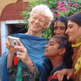 Ehrenamt im Ruhestand: Eine ältere deutsche Frau zeigt drei pakistanischen Frauen Fotos auf ihrer Kompaktkamera. Ehrenamtliches Engagement im Alter vermittelt u.a. der Senior Expert Service, Freiwilligenagenturen oder gemeinnützige Organisatonen und Stiftungen. Foto: SES Bonn