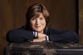 Was bleibt, Christine Westermann? Porträt der Moderatorin Christine Westermann an einem Holztisch sitzend, das Kinn aus die Hände gelegt. Die Journalistin erzählt in ihrem neuen Buch über das Abschiednehmen. Im Interview spricht sie über die Frage