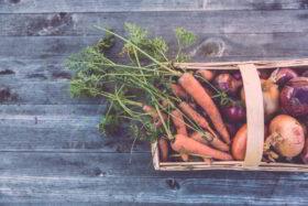 Glücksforschung - Warum schenken glücklich macht: Draufsicht auf einem Korb mit einem frischen Bund Möhren und Zwiebeln auf einem Holzboden. Wer mit Gemüse verschenkt, um Kunden zu locken, hat selten Glück. Wer selbstlos und ohne Vorsatz schenkt, wird selbst glücklicher. Foto: Markus Spiske on Unsplash