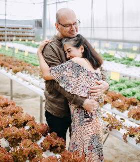Glücksforschung - Warum schenken glücklich macht: Ein Mann und eine Frau in einem Gewächshaus umarmen sich innig. Schenken stillt ein Ur-Bedürfnis. Wir wollen verbunden sein. Foto: Anthony Tran on Unsplash