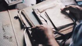 So gelingt die Lebensbilanz: Nahaufnahme einer Hand, die alte Dokumente sortiert. Es gibt verschiedene Techniken, mit denen man auf das Leben zurückschauen und Entscheidungen, für das, was bleibt, treffen kann. Foto: Duong Tran Quoc on Unsplash
