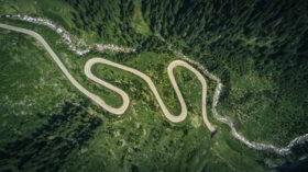 So gelingt die Lebensbilanz: Draufsicht auf eine Straße, die, nach dem sie sich durch Berge schlängelt, in einem Tunnel endet. Ein neuer Blick aufdie eigene Vergangenheit hilft, den roten Faden zu erkennen. Foto: Jaromir Kavan on Unsplash