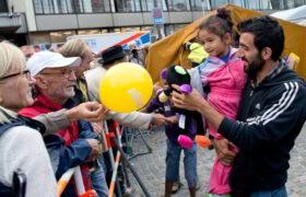 Glücksforschung - Warum schenken glücklich macht: Flüchtlinge, die kurz zuvor mit einem Zug angekommen sind, werden im September 2015 auf dem Hauptbahnhof in München (Bayern) von zahlreichen Menschen begrüßt. Ehrenamtliche Flüchtlingshelfer fühlen sich häufig