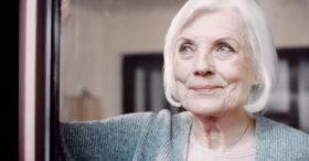 Den Nachlass regeln: Nahaufnahme einer älteren Frau mit weißem, halblangem Harr, die am Fenster steht und zufrieden lächelnd in die Ferne schaut. Wer seinen Nachlass regelt, entleidgt sich einer großen Last.Foto: Initiative