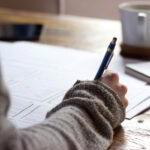 Den Nachlass regeln: Hand einer Frau beim Schreiben des Testaments. Wer sein Testament schreibt und seinen Letzten Willen macht, entledigt sich einer großen Last. Foto: Green Chameleon on Unsplash