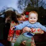 Wie Großeltern Werte weitergeben: Blick durch ein Fenster, an dem eine Großmutter mit rotbraunem Haar ihren kleinen rothaarigen Enkel auf dem Arm hält. Das Kind lacht durch die Scheibe der Mutter zu. Drei Generationen in einem Bild. Neue Großeltern sind aktiv und jugendlich. In Prinzip Apfelbaum. Magazin über das, was bleibt. Foto: pixabay