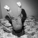 Prinzip Apfelbaum. Magazin über das, was bleibt. Ausgabe 2: FAMILIE. Ein Kind turnt, die Füße in die Luft, den Kopf in den Kissen, auf seinem mit Blumenmuster bezogenem Bett herum. Familie, das bedeutet sich freuen, wetteifern, streiten, versöhnen. Foto: Paolo Pellegrin / Magnum Photos / Agentur Focus