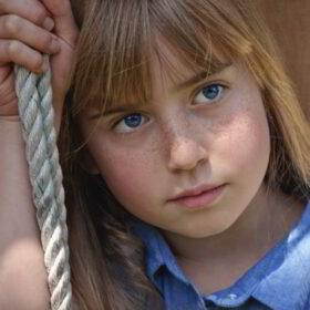 Das tut gut: Großaufnahme eines traurig schauenden Mädchen mit rotblondem Haar und Sommersprossen. Mit dem Kinderreport 2018 setzt sich das Deutsche Kinderhilfswerk gegen Kinderarmut ein. DKHW ist Mitglied der Initiative