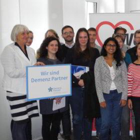 """Das tut gut: Eine Gruppe Frauen und Männer mit einem Schild """"Wir sind Demenz Partner"""" – dank der Initiative der Deutschen Alzheimer Gesellschaft werden Menschen überall in Deutschland im Umgang mit Demenzkranken geschult. Die gemeinnützige Organisation ist Mitglied der Initiative"""