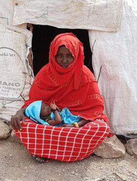 Das tut gut: Eine Frau gehüllt in rotes Tücher sitzt im ostafrikanischen Dschibuti auf dem trockenen Boden vor einem Zelt, im Schoss ihr Baby – Dank der Aufklärungsarbeit der Johanniter Auslandshilfe das erste Mädchen ihres Dorfes, das nicht beschnitten wurde. Johanniter sind Mitglied der Initiative