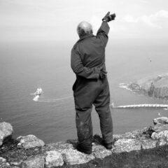 Prinzip Apfelbaum. Ausgabe 3: ABSCHIED. Rückenansicht eines älteren Mannes, der auf einer Steinmauer hoch über dem Meer steht und einem abfahrenden weißen Boot hinterherwinkt. Worte, Orte und neue Wege für den Abschied gibt es im Magazin über das, was bleibt. Foto: Stuart Franklin / Magnum Photos / Agentur Focus