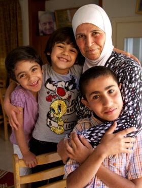 Das tut gut: Eine SOS-Mutter umarmt drei Kinder. Mitten im Krieg finden die Kriegswaisen im SOS-Kinderdorf bei Damaskus ein neues Zuhause. SOS Kinderdörfer weltweit ist Mitglied der Initiative
