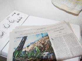 Erinnern und vom Leben erzählen: Eine Zeitung liegt auf einer Waschmaschine. Die Nachrufeseite des Berliner Tagesspiegels erinnert jede Woche an Verstorbene. Redakteur David Ensikat führt dazu viele Gespräche mit Trauernden. Erinnern und Erzählen sind Teil der Trauerarbeit und helfen beim Abschiednehmen. In: Prinzip Apfelbaum. Magazin über das, was bleibt. Foto: Studio Hoekstra / Corinna Hengelein