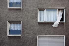 Trauern, wie wir es wollen: Eine Gardine weht aus einem offenen Fenster eines Plattenbaus. Symbolbild: Alternativen Bestatter setzen auch auf alte Bräuche wie Totenbett, Fenster öffnen, Uhren anhalten. Ihr Rat: Nicht fragen, was erlaubt ist und was üblich, sondern schauen, womit man sich selbst wohl fühlt, um Abschied zu nehmen. In: Prinzip Apfelbaum. Magazin über das, was bleibt. Foto: Mr. Nico/Photocase
