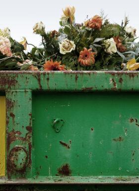 Trauern, wie wir es wollen: Welke Blumen in einem grünen Container. Symbolbild: Immer mehr Menschen fühlen sich mit üblichen Bestattungsritualen nicht mehr wohl. Alternative Bestatter helfen, individuelle Rituale zu entwickeln. In: Prinzip Apfelbaum. Magazin über das, was bleibt. Foto: designritter/photocase