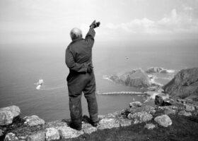 Prinzip Apfelbaum. Magazin über das, was bleibt. Ausgabe 3: Abschied. Schwarzweiß-Bild zeigt die Rückansicht eines älteren Mannes, der auf den Klippen hoch über dem Meer steht und einer abfahrenden Fähre nachwinkt. England, Lundy Island, 2005. Abschiede begleiten uns von klein auf. Doch das Loslassen müssen wir lebenslang lernen. Foto: Stuart Franklin / Magnum Photos / Agentur Focus