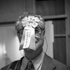 Prinzip Apfelbaum. Magazin über das, was bleibt. Ausgabe 4: Ehrensache. Schwarzweiß-Bild zeigt den US-Amerikanischen Fotograf Elliott Erwitt, in die Kamera lächelnd mit einer Ehrenschleife auf der Stirn. Tokyo, 1997. Gutes tun, das ist für viele Ehrensache, über Anerkennung freuen wir uns trotzdem. Foto: Peter Marlow/Magnum Photos/Agentur Focus