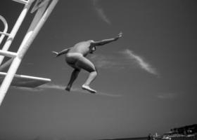 Prinzip Apfelbaum. Magazin über das, was bleibt. Ausgabe: Entscheiden. Schwarzweiß-Bild eines Jungen in Badehose, der von einem Elfmeterturm springt, Untersicht. French Rivera, 1992. Gute Entscheidungen zu treffen, ist nicht immer leicht. Foto: Peter Marlow/Magnum Photos/Agentur Focus