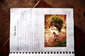 Erinnerung gestalten: Seite eines ugandischen Memory Book, ein Kinderfoto und Erinnerungen an die Geburt. Erinnerungen sind für Trauernde der wertvollste Besitz. In: Prinzip Apfelbaum. Magazin über das, was bleibt. Foto: Álvaro Laiz und David Rengel