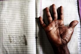 Erinnerung gestalten: Seite eines ugandischen Memory Book, darauf eine Hand. Erinnerungen lassen sich gestalten, so dass sie Trauernde begleiten und ihm Kraft geben können. In: Prinzip Apfelbaum. Magazin über das, was bleibt. Foto: Álvaro Laiz und David Rengel