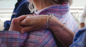 Trauernden beistehen: Eine ältere Frau legt einer anderen die Hand auf die Schulter, Nahaufnahme. Im Umgang mit Trauernden sind viele hilflos. Trost gibt es nicht, aber da sein hilft. Rat von Trauerbegleiter Roland Kachler. – In: Prinzip Apfelbaum. Magazin über das, was bleibt. Foto: carly.ciardullo/Twenty20