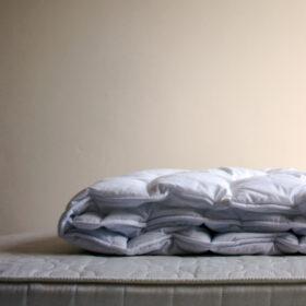 Handeln im Trauerfall: Zusammengelegte Bettdecke auf einer Matratze, beides ohne Bezug. Stirbt ein Mensch, muss die Trauer oft warten. Denn für Angehörige gibt es viel zu erledigen. Eine Übersicht. In: Prinzip Apfelbaum. Magazin über das, was bleibt. Foto: ohneski/Photocase.de