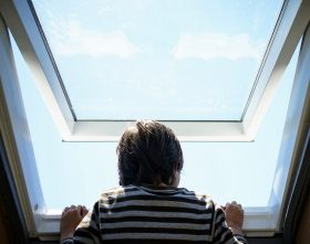 Jeder trauert anders: Rückansicht eines Jungens der eine Dachfenster öffnet, zu sehen ist blauer Himmel. Symbolbild. Trauer verläuft nicht in festen Phasen. In: Prinzip Apfelbaum. Magazin über das, was bleibt. Foto: ESB Professional/Shutterstock.com