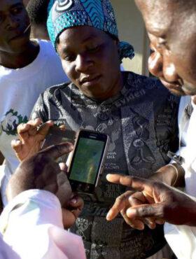 """Das tut gut: Kleinbauern in Simbabwe schauen gemeinsam auf ein Smartphone. Mit der App Kurima Mari der Welthungerhilfe Kleinbauern lernen sie Anbaumethoden zu verbessern. Die Welthungerhilfe ist Mitglied der Initiative """"Mein Erbe tut Gutes"""