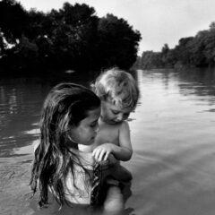 Prinzip Apfelbaum. Magazin über das, was bleibt. Ausgabe 8: ERINNERUNG. Der zweijährige Isaac Towell wird von seiner älteren Schwester Naomi vorsichtig in den Sydenham River getragen, um ihn das erste Mal mit dem Wasser in Berührung zu bringen. Ontario, 1996. Foto: © Larry Towell / Magnum Photos / Agentur Focus