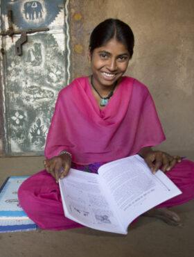 """Das tut gut: Die 19-jährige Sheela präsentiert lachend ihre Lehrbücher. Sie ist eine der jungen Frauen, die ChildFund in Indien dabei unterstützt, eine höhere Bildung zu erlangen. Das Kinderhilfswerk ist Mitglied der Initiative """"Mein Erbe tut Gutes"""". Foto: Jake Lyell / ChildFund"""