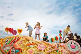 Utopien: Vier Kinder tummeln sich in einer Landschaft aus Süßigkeiten. Symbolbild: Es braucht Phantasie, um von einer besseren Zukunft zu träumen und diese zu gestalten. Alles könnte anders sein. – In: Prinzip Apfelbaum. Magazin über das, was bleibt. Foto: Jan von Holleben