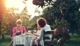 Vermächtnis: Großmutter, Tochter und Enkelkinder sitzen an einem Tisch unter Apfelbäumen. Symbolbild: Mit einer Testamentsspende lässt sich Bleibendes schaffen, dass immer wieder Früchte trägt. – In: Prinzip Apfelbaum. Magazin über das, was bleibt. Foto: Marissa Price on Unsplash