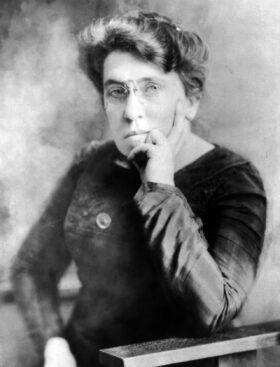 Zitat: Schwarzweiß-Fotografie von Emma Goldman, auf einem Stuhl sitzend, das Kinn auf die linke Hand gestützt, 1911. Prinzip Apfelbaum – Magazin über das, was bleibt. Ausgabe: Zukunft. Foto: T. Kajiwara, Wikipedia Commons, gemeinfrei