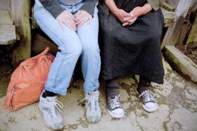 Erzähl mal: Beine einer jungen und einer ältere Frau, nebeneinander auf einer Bank sitzend, beide tragen Turnschuhe. Erinnerungen halten Vergangenheit lebendig. Eine Anregung zum Dialog zwischen Alt und Jung. In: Prinzip Apfelbaum. Magazin über das, was bleibt. Foto: MBierschenk / photocase.de