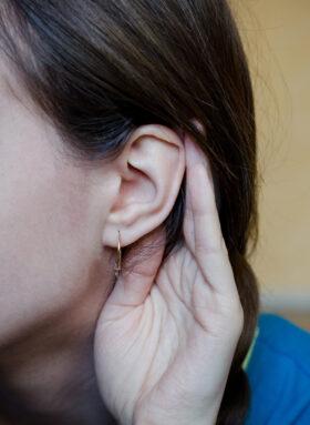 Erzähl mal: Eine junge Frau hält die Hand am Ohr, um besser zu hören. Viele Menschen möchten ihre Erfahrungen weitergeben, oft fragen auch die Jüngeren die Älteren. Gelebte Erinnerungen sind ein Schatz. Eine Anregung zum Dialog. In: Prinzip Apfelbaum. Magazin über das, was bleibt. Foto: Him_muse via Twenty20