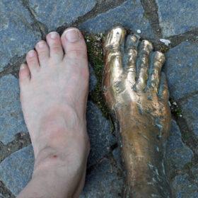 Im Gedächtnis bleiben: Linken Fuß eines Erwachsenen neben dem rechten Fuß einer Statue. Manche wollen mit dem Erbe Gutes tun, um in Erinnerung zu bleiben oder einem geliebten Menschen zu gedenken. In: Prinzip Apfelbaum. Magazin über das, was bleibt. Foto: Stihl024 / photocase.de