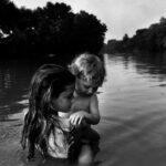 Prinzip Apfelbaum. Magazin über das, was bleibt. Ausgabe 8: ERINNERUNG. Kanada, Ontario, 1996. Der zweijährige Isaac Towell wird von seiner älteren Schwester Naomi vorsichtig in den Sydenham River getragen, um ihn das erste Mal mit dem Wasser in Berührung zu bringen. Foto: Larry Towell / Magnum Photos / Agentur Focus