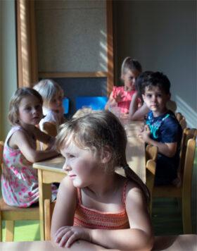 Heimat mit Zukunft: Ein kleines Mädchen blickt aus dem Fenster des Kindergartens in Nebelschütz. Symbol der Wiedergeburt: Während andernorts junge Menschen abwandern, ist die sorbische Gemeinde ein Dorf mit Zukunft. In: Prinzip Apfelbaum. Magazin über das, was bleibt. Foto: Antonina Gern