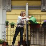 Engagement unter Nachbarn: Eine Frau gießt die Balkonblumen ihrer Nachbarn. Tatsächlich können wir selbst auch viel dafür tun, uns zuhause zu fühlen und uns eine Heimat zu schaffen, meint Henning von Vieregge. In: Prinzip Apfelbaum. Magazin über das, was bleibt. Foto: nebenan.de