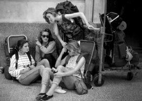 Prinzip Apfelbaum. Magazin über das, was bleibt. Ausgabe 9: Heimat. GB, England, 1985: Eine Gruppe junger Backpackerinnen wartet am Flughafen. Symbolbild für das Aufbrechen, Suchen und Ankommen. Heimat ist Ort, Sehnsucht und Bedürfnis. Foto: Eve Arnold / Magnum Photos / Agentur Focus