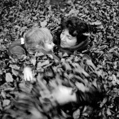 Prinzip Apfelbaum. Magazin über das, was bleibt. Ausgabe 10: Loslassen. England, Somerset, 1986: Frau und Kind wälzen sich im Herbstlaub. Symbolbild für das Loslassen und Verzeihen, für Abschied und Weitergeben. Foto: Stuart Franklin / Magnum Photos / Agentur Focus