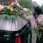 Keine Angst vor dem Tod: USA, New York City, 2003: Nach einer Beerdigung sammeln heitere Frauen Blumen vom Leichenwagen als Erinnerung an ihre Freundin. Symbolbild: Dem Tod gelassen entgegenzusehen, heißt, sich dem Leben zu widmen. In: Prinzip Apfelbaum. Magazin über das, was bleibt. Foto: Paul Fusco/Magnum Photos/Agentur Focus