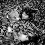 Prinzip Apfelbaum. Magazin über das, was bleibt. Ausgabe 10: Loslassen. England, Somerset, Quantock Hills, 1986: Mutter und dreijährige Tochter umarmen sich und wälzen sich im Herbstlaub. Symbolbild für das Loslassen und Verzeihen, für Abschied und Weitergeben. Foto: Stuart Franklin / Magnum Photos / Agentur Focus