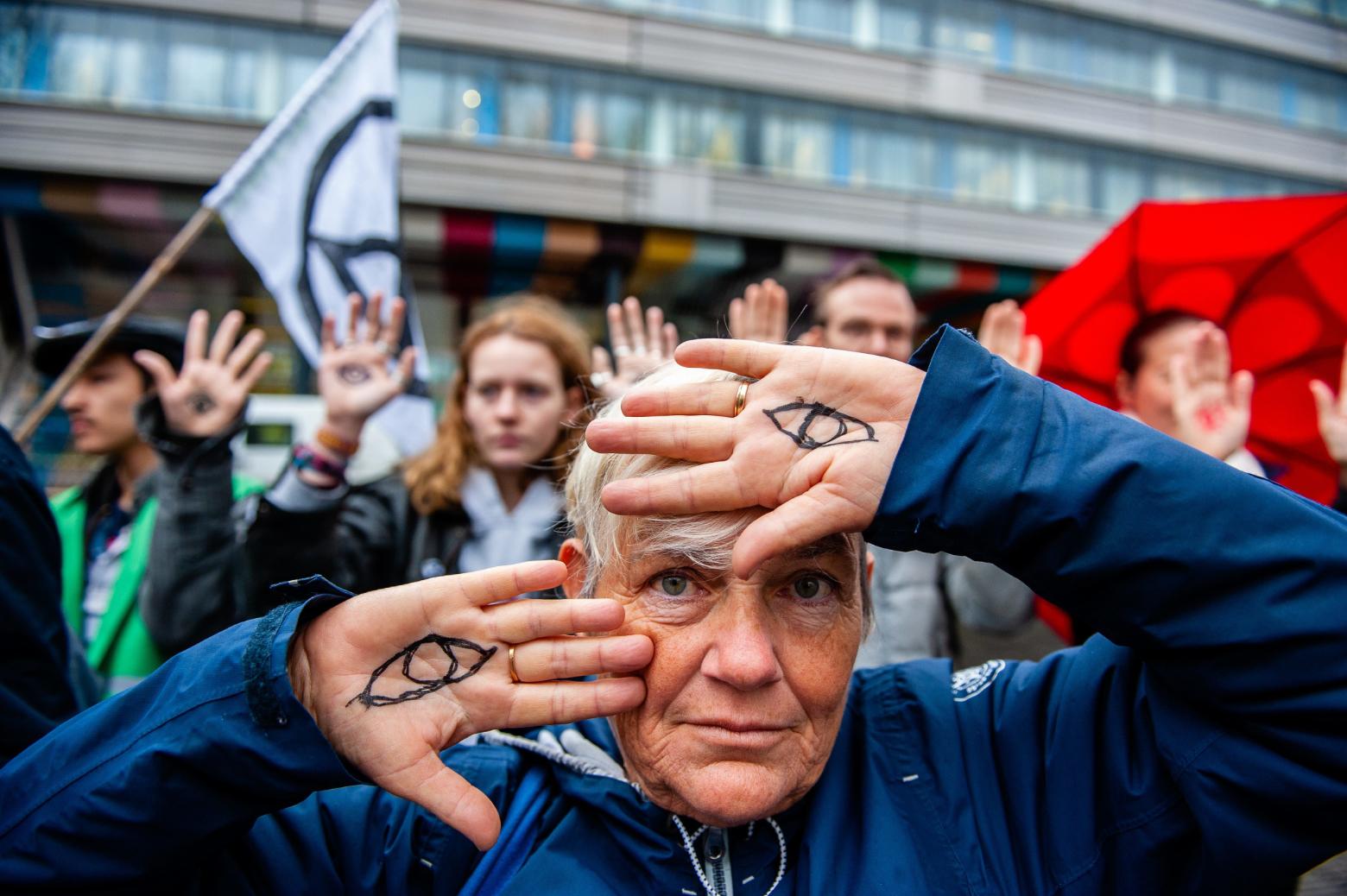 Vom Wissen zum Wandel: Demonstrantin bei Klimaprotesten in Den Haag zeigt Handflächen, darauf gemalt zwei Augen. Symbolbild: Erst wer erkennt, dass Veränderungen nötig sind, um Gutes zu bewahren, ist zum Wandel bereit. In: Prinzip Apfelbaum. Magazin über das, was bleibt. Foto: picture alliance/dpa
