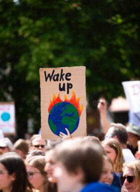"""Vom Wissen zum Wandel: Pappschild mit der Aufschrift """"Wake Up"""" und einer gemalten Erde in Flammen bei Klimaproteste in Berlin. Wandel beginnt im Kopf jedes Einzelnen. Ein kleiner Funke kann eine ganze Bewegung entfachen. In: Prinzip Apfelbaum. Magazin über das, was bleibt. Foto: Markus Spiske on Unsplash"""