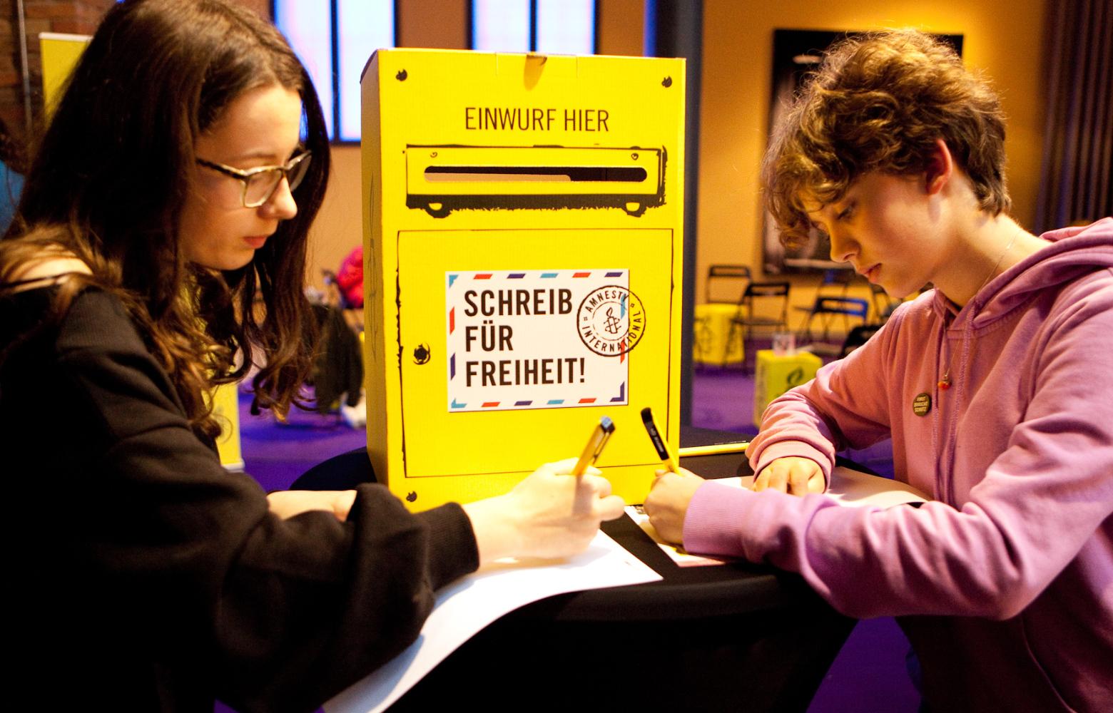 Kleines Erbe: Zwei Jugendliche stehen an einem Stehtisch und schreiben einen Brief beim Amnesty-Briefmarathon. Möglich auch durch kleine Beträge als Testamentsspende oder Zustiftung. – In: Prinzip Apfelbaum. Magazin über das, was bleibt. Foto: Amnesty