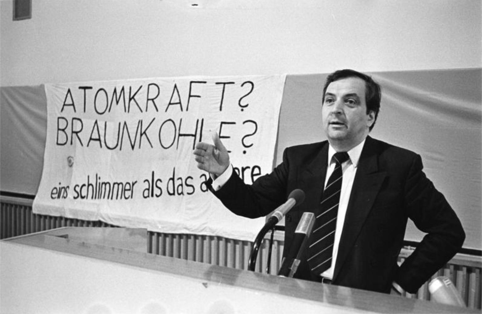 Leben für Wandel: Umweltminister Klaus Töpfer bei einer Rede in Cottbus, 1990. Dahinter ein Transparent mit der Aufschrift