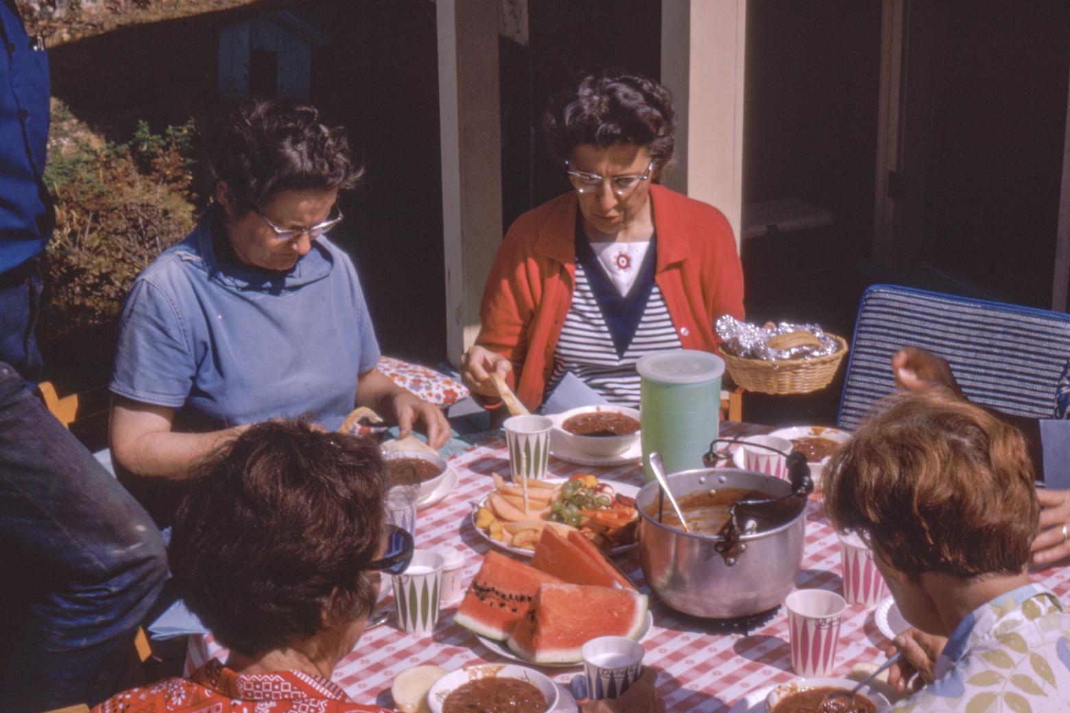 Dinge unseres Lebens: Historische Aufnahme einer Familie beim Essen, auf dem Tisch eine karierte Decke. Symbolbild: Was übrig bleibt vom Leben. In den Dingen verdichten sich Geschichten. Sie blühen auf, wenn man die Gegenstände in die Hand nimmt. In: Prinzip Apfelbaum. Magazin über das, was bleibt. Foto: Annie Spratt on Unsplash