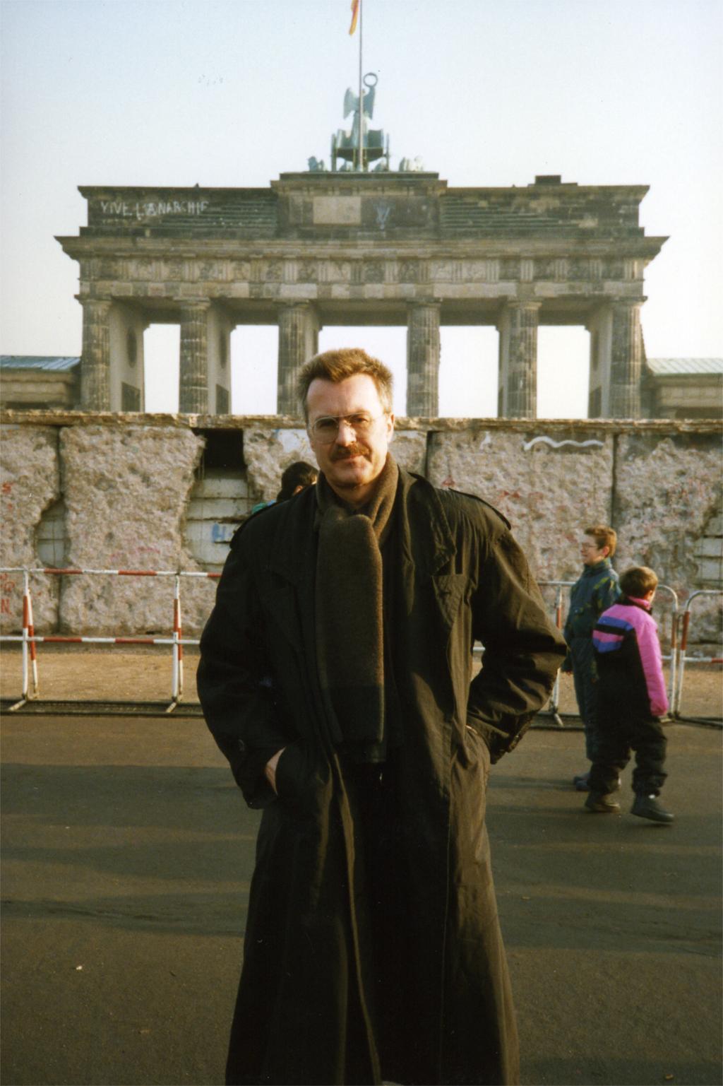 Geschichte wird gemacht: Porträt eines Mannes vor Berliner Mauer und Brandenburger Tor, Besuch aus dem Westen, Februar 1990. Zeitzeugen tragen persönlich Erlebtes weiter. Sie helfen, Geschichte zu verstehen und Zukunft zu gestalten. Warum ist das wichtig? In: Prinzip Apfelbaum. Magazin über das, was bleibt. Foto: Freya Singer/CC BY-NC-ND